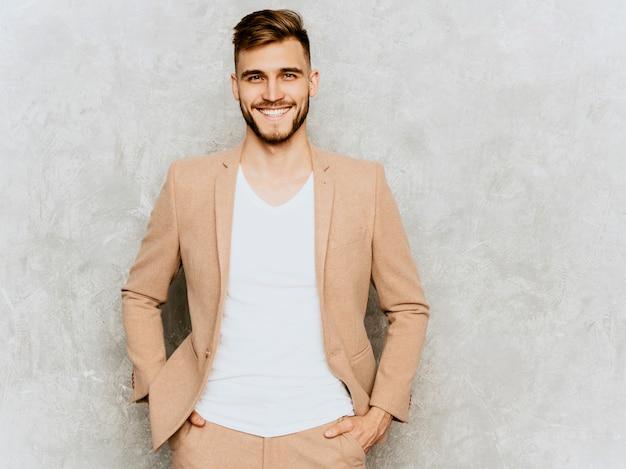 Retrato do modelo de empresário de hipster sorridente bonito vestindo terno bege casual.