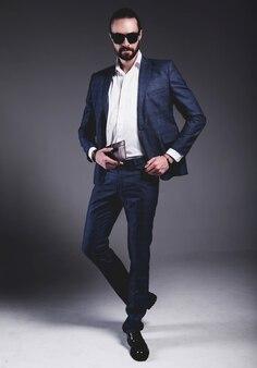 Retrato do modelo de empresário de moda hipster elegante bonito vestido com elegante terno azul em óculos de sol posando em cinza