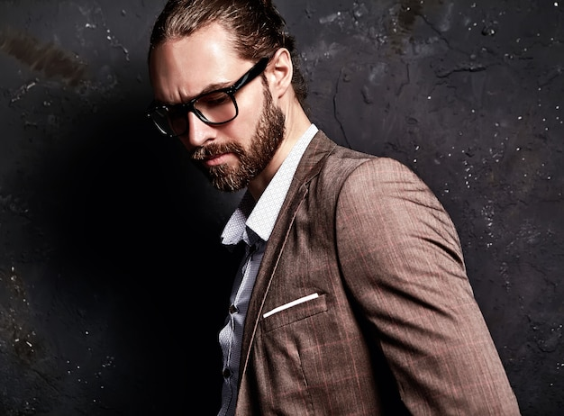 Retrato do modelo de empresário de moda hipster elegante bonito vestido com elegante terno marrom em copos perto da parede escura
