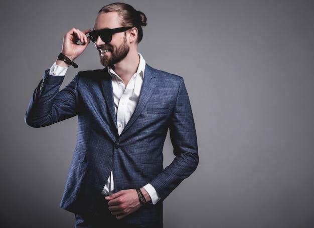 Retrato do modelo de empresário de moda hipster elegante bonito vestido elegante terno azul posando em cinza