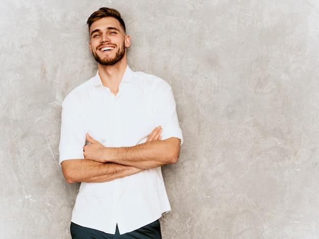 Retrato do modelo de empresário de sorriso bonito hipster vestindo camisa casual de verão branco.