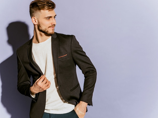 Retrato do modelo de empresário hipster confiante bonito vestindo terno preto casual.