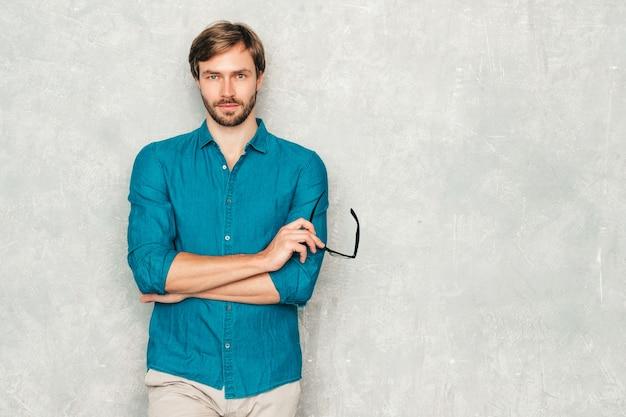 Retrato do modelo de empresário lumbersexual bonito hipster confiante vestindo roupas de camisa jeans casual.