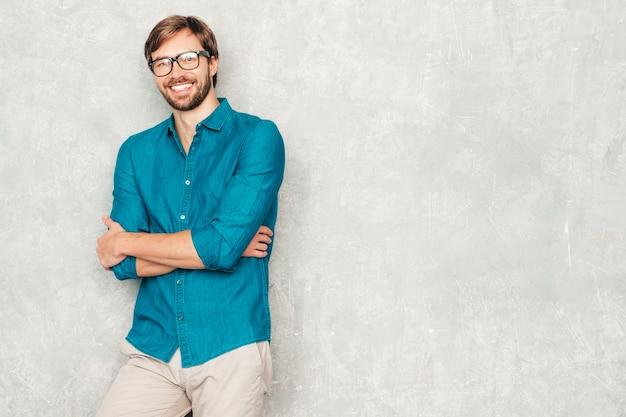 Retrato do modelo de empresário lumbersexual hipster sorridente bonito, vestindo roupas de camisa jeans casual.