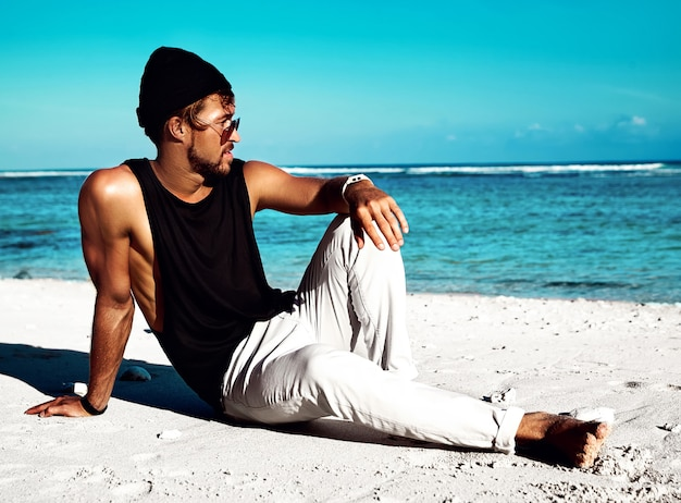 Retrato do modelo de homem bonito moda banhos de sol hipster vestindo roupas casuais em camiseta preta e óculos de sol, sentado na areia branca, perto do céu e oceano azul