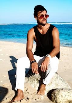 Retrato do modelo de homem bonito moda hipster banhos de sol vestindo roupas casuais em camiseta preta e óculos de sol, sentado nas pedras