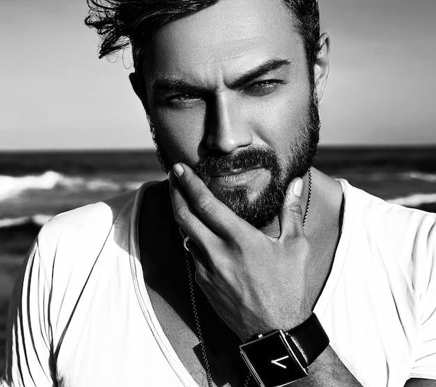 Retrato do modelo de homem bonito moda vestindo roupas brancas, posando no mar azul