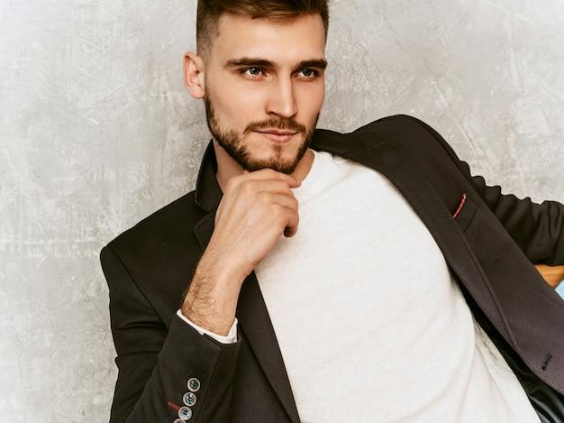 Retrato do modelo de homem de negócios sério bonito hipster vestindo terno preto casual. sentado na cadeira no interior