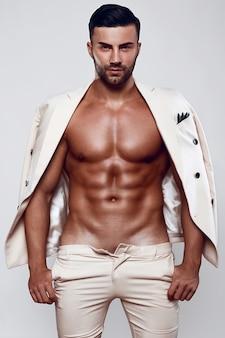 Retrato do modelo de homem elegante e brutal em um terno leve isolado no fundo branco, sessão de fotos