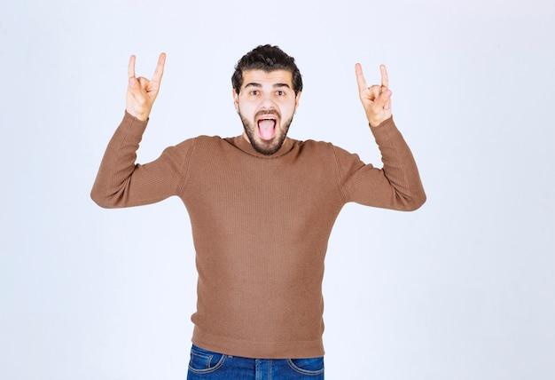 Retrato do modelo de jovem bonito homem gritando fazendo gesto de pedra com as duas mãos. foto de alta qualidade