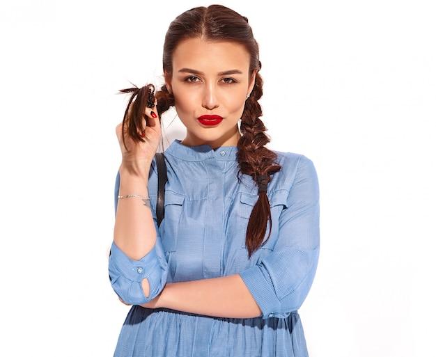 Retrato do modelo de jovem sorridente feliz com maquiagem brilhante e lábios vermelhos com duas tranças nas mãos no vestido azul colorido do verão
