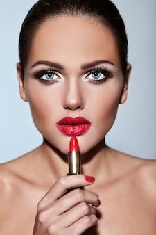 Retrato do modelo de menina bonita com maquiagem de noite com pomada vermelha nas mãos