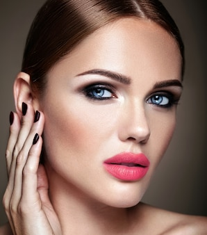 Retrato do modelo de menina bonita com maquiagem de noite e penteado romântico, tocando a pele dela. lábios rosados