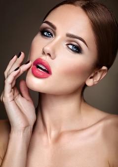 Retrato do modelo de menina bonita com maquiagem de noite e penteado romântico. tocando seus lábios vermelhos