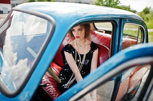 Retrato do modelo de menina bonita moda encaracolado com maquiagem brilhante em estilo retro, sentado em um carro antigo