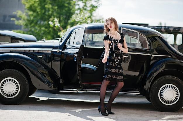 Retrato do modelo de menina bonita moda encaracolado sexy com maquiagem brilhante em estilo retro perto de carros antigos