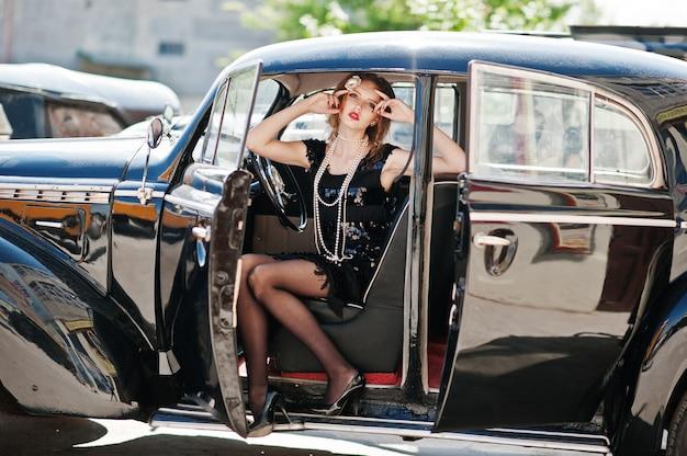 Retrato do modelo de menina bonita moda sexy com maquiagem brilhante em estilo retro, sentado no carro antigo