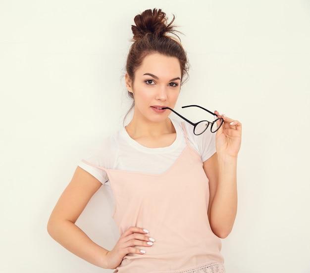 Retrato do modelo de menina jovem morena linda com maquiagem nude em roupas de verão colorido rosa hipster posando perto da parede. óculos cortantes