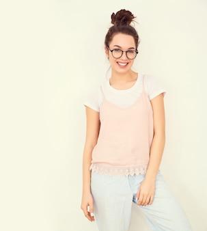 Retrato do modelo de menina jovem morena linda com maquiagem nude em roupas de verão colorido rosa hipster posando perto da parede. olhando feliz