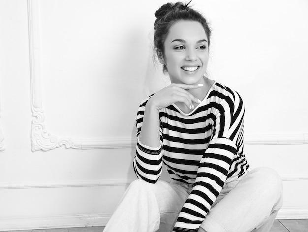 Retrato do modelo de menina jovem morena linda com maquiagem nude em roupas de verão hipster posando perto da parede. sentado no chão