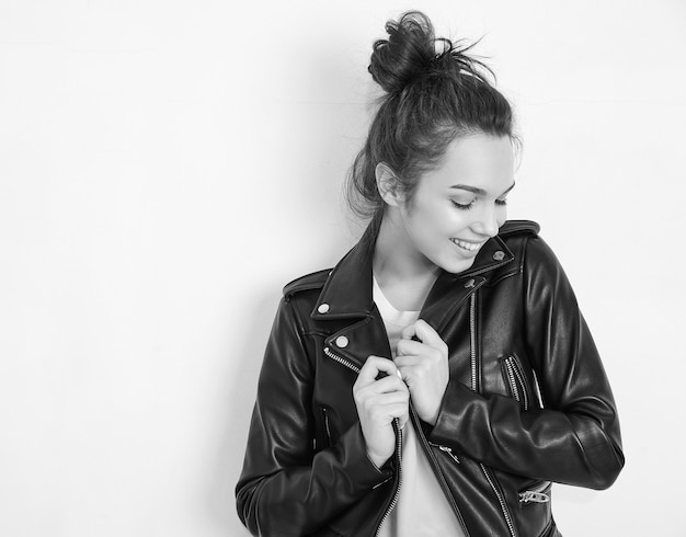 Retrato do modelo de menina jovem morena linda com maquiagem nude, vestindo jaqueta de couro motociclista hipster de verão posando perto da parede.