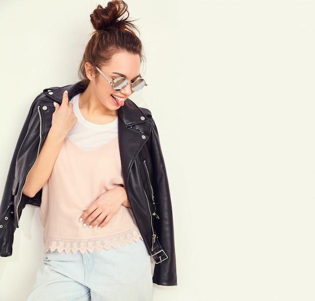 Retrato do modelo de menina jovem morena linda com maquiagem nude, vestindo roupas de verão hipster motociclista jaqueta de couro em óculos de sol posando perto da parede. mostrando a língua