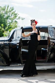 Retrato do modelo de menina moda morena sexy bonita com maquiagem brilhante em estilo retro perto de carros antigos com um cigarro na mão.