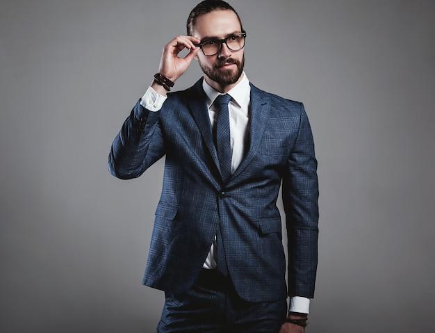 Retrato do modelo de moda bonito empresário vestido elegante terno azul com óculos