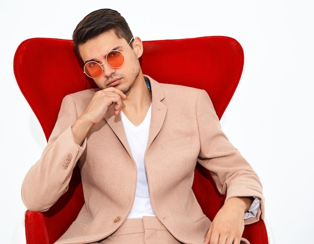 Retrato do modelo de moda elegante empresário elegante vestido elegante luz rosa terno sentado na cadeira vermelha. metrosexual