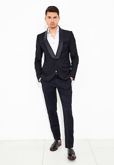 Retrato do modelo de moda elegante empresário elegante vestido elegante terno clássico preto posando. metrosexual