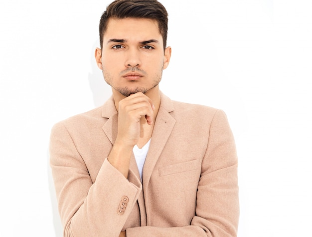 Retrato do modelo de moda elegante empresário elegante vestido elegante terno rosa luz posando. metrosexual
