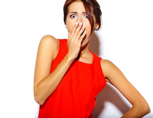 Retrato do modelo de moda jovem bonito em um vestido vermelho em uma parede branca