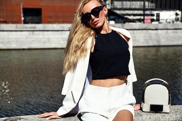 Retrato do modelo de moda moderna empresária sexy terno branco com bolsa posando no fundo da rua atrás do céu azul
