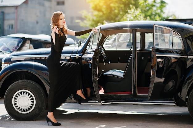 Retrato do modelo de moda sexy linda garota com maquiagem brilhante em estilo retro, perto de carros antigos com um cigarro na mão.