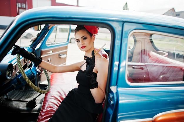Retrato do modelo de moda sexy linda garota com maquiagem brilhante em estilo retro, sentado no carro antigo com um cigarro na mão.