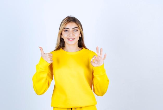 Retrato do modelo de mulher bonita apontando para cima e fazendo um gesto de ok