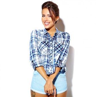 Retrato do modelo de mulher bonita camisa casual verão xadrez sem maquiagem na parede branca