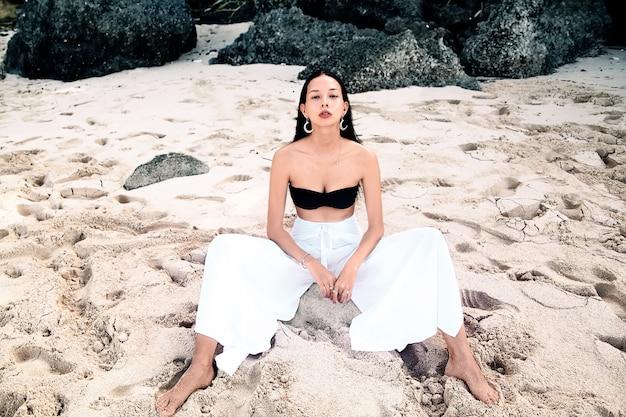 Retrato do modelo de mulher bonita caucasiano com cabelos longos escuros nas calças clássicas de pernas largas, sentado na praia de verão com areia branca perto de pedras