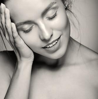 Retrato do modelo de mulher bonita com maquiagem diária fresca e lábios vermelhos, tocando a cabeça