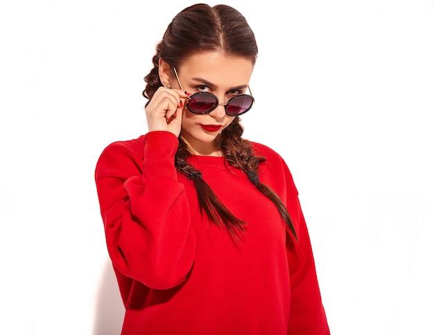 Retrato do modelo de mulher feliz sorridente jovem com maquiagem brilhante e lábios coloridos com duas tranças e óculos de sol em roupas de verão vermelho isoladas. atrás de óculos de sol da moda