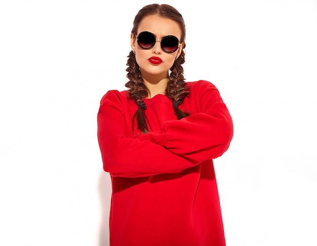 Retrato do modelo de mulher feliz sorridente jovem com maquiagem brilhante e lábios coloridos com duas tranças e óculos de sol em roupas de verão vermelho isoladas. braços cruzados