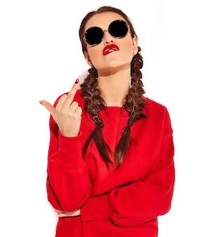 Retrato do modelo de mulher feliz sorridente jovem com maquiagem brilhante e lábios coloridos com duas tranças e óculos de sol em roupas de verão vermelho isoladas. mostrando sinal foda-se