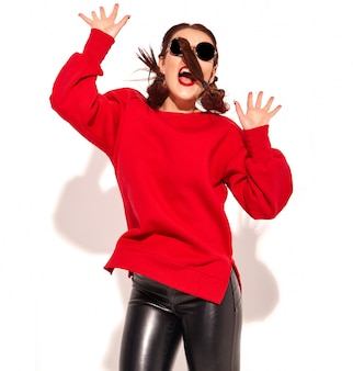 Retrato do modelo de mulher feliz sorridente jovem com maquiagem brilhante e lábios coloridos com duas tranças e óculos de sol em roupas de verão vermelho isoladas.