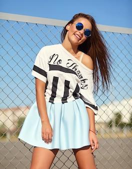 Retrato do modelo de mulher jovem e bonita sorridente elegante glamour engraçado elegante em roupas casuais de verão hipster brilhante posando na rua atrás de grade de ferro e céu azul