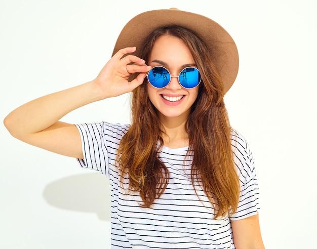 Retrato do modelo de mulher jovem rindo elegante em roupas de verão casual com chapéu marrom isolado na parede branca