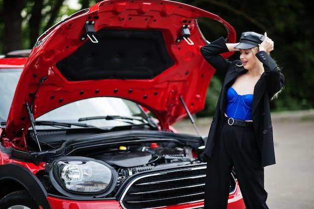 Retrato do modelo de mulher loira linda moda sexy na tampa e em todo preto com maquiagem brilhante perto do carro vermelho da cidade com capô aberto.