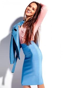 Retrato do modelo de mulher morena sorridente caucasiano bonito em roupas elegantes de verão rosa e azul brilhante, isolado no fundo branco
