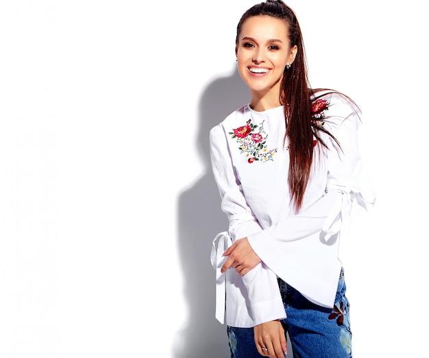 Retrato do modelo de mulher morena sorridente caucasiano bonito na blusa branca e calça jeans azul elegante de verão