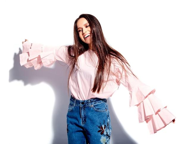 Retrato do modelo de mulher morena sorridente caucasiano bonito na blusa rosa brilhante e verão azul jeans elegante