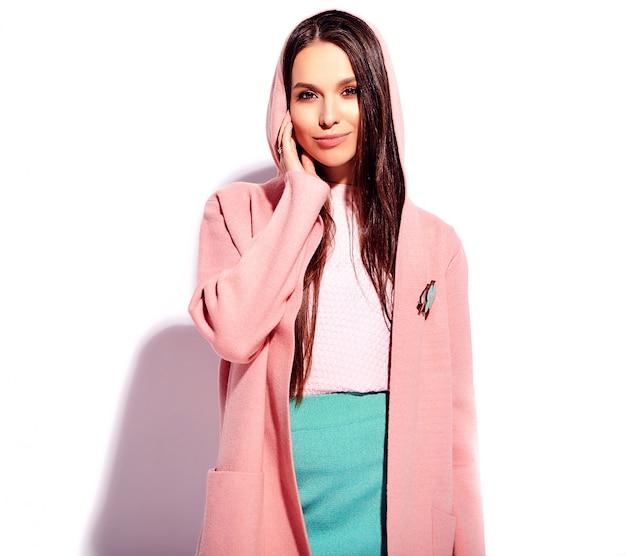 Retrato do modelo de mulher morena sorridente caucasiano bonito no sobretudo rosa brilhante e saia azul elegante de verão isolada no fundo branco